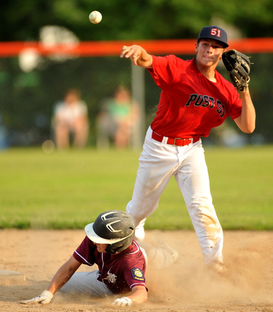 Post 51's A.J. Godin turns the double play as Franklin County's Scott Hall tries to break it up Tuesday in the American Legion Zone 2 championship at Memorial Field in Skowhegan.