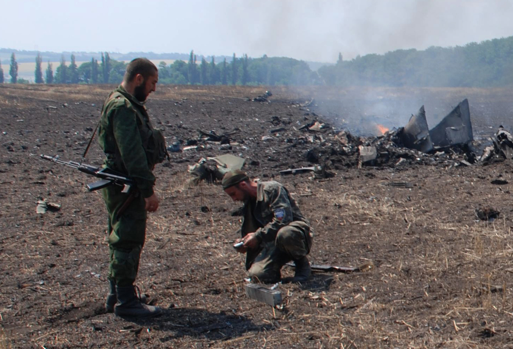 The Associated Press In this framegrab made from a video provided by press service of the rebel Donetsk People's Republic and icorpus.ru,  pro-Russians collect parts of the burning debris of a Ukrainian military fighter jet, shot down at Savur Mogila, eastern Ukraine, Wednesday.