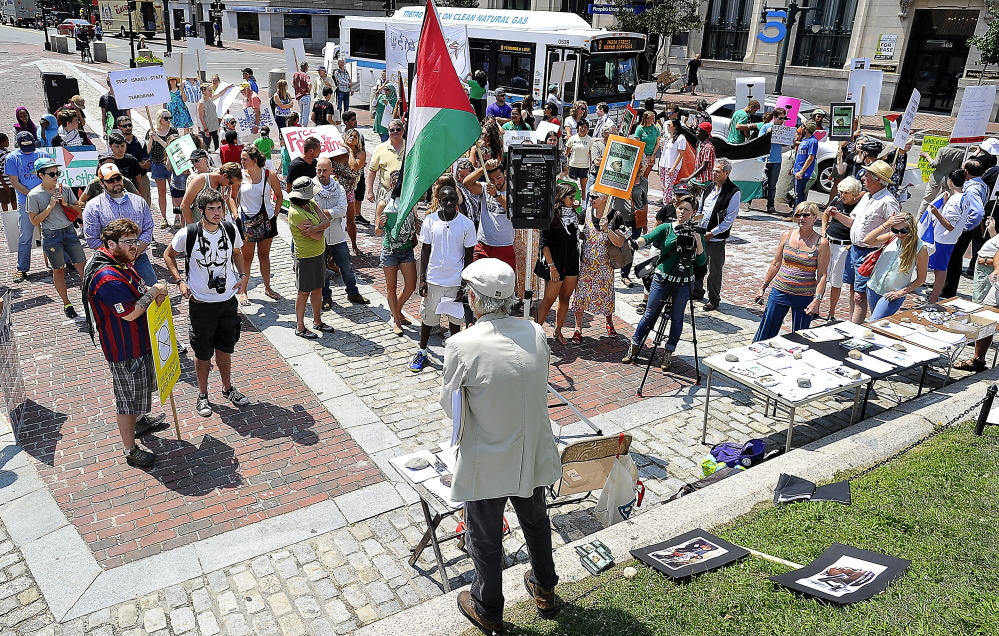PORTLAND, ME - JULY 24: Bob Schaible of Buxton. chair of Maine Voices for Palestinian Rights, urges the signing of petitions by the Pro-Palestinian protesters who condemn Israel's bombing of Gaza in response to Hamas'  bombing of Israel in a protest in Monument Square. (Photo by Gordon Chibroski/Staff Photographer)