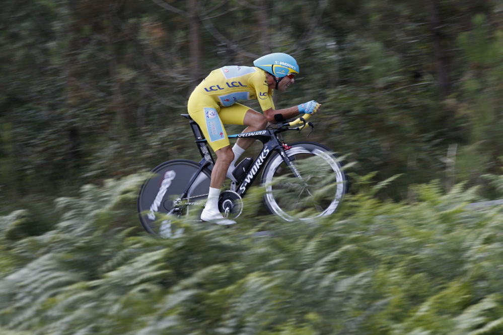 Italy's Vincenzo Nibali, wearing the overall leader's yellow jersey, strains during the twentieth stage of the Tour de France cycling race, an individual time-trial over 54 kilometers (33.6 miles) with start in Bergerac and finish in Perigueux, France, Saturday.