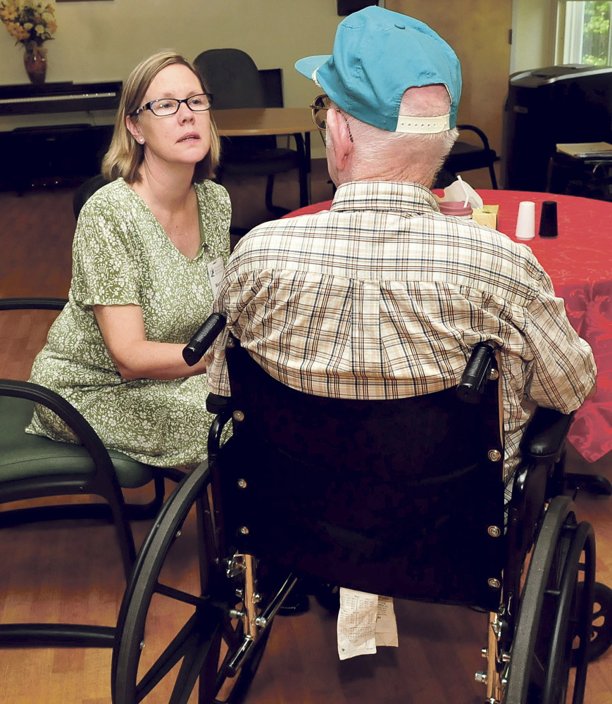 Mary Ford, owner of Pittsfield Rehab and Nursing, speaks with a resident on Wednesday. The nursing home will close by September.