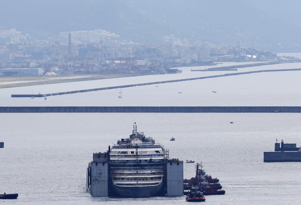 The wreck of the Costa Concordia cruise ship is towed by tugboats towards Genoa's harbor, Italy, Sunday.