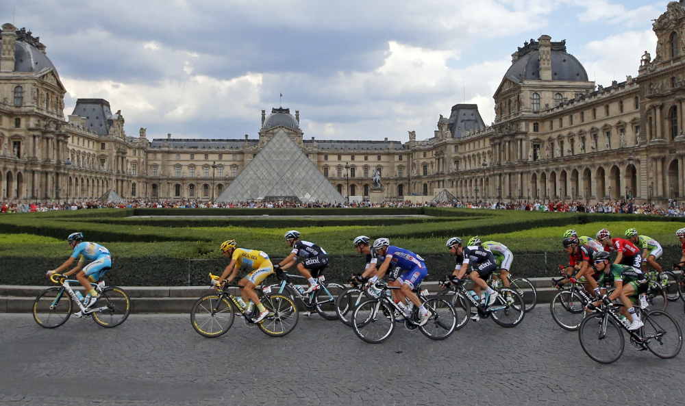 The pack, with Vincenzo Nibali of Italy, wearing the overall leader's yellow jersey, left, rides through the courtyard of the Louvre museum, during the 21st and last stage of the Tour de France cycling race with finish in Paris, France, Sunday.