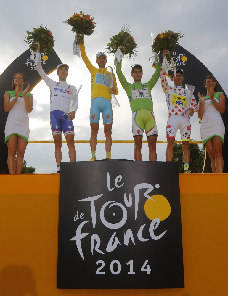 2014 Tour de France cycling race winner Vincenzo Nibali of Italy, wearing the overall leader's yellow jersey, Peter Sagan of Slovakia, wearing the best sprinter's green jersey, Rafal Majka of Poland, wearing the best climber's dotted jersey, and Thibaut Pinot of France, wearing the best young rider's white jersey, celebrate on the podium in Paris, France, Sunday.