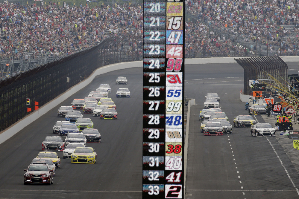 Cars on different pit strategies enter pit lane while others stay on the track in a caution period during the NASCAR Brickyard 400 auto race at Indianapolis Motor Speedway in Indianapolis, Sunday.