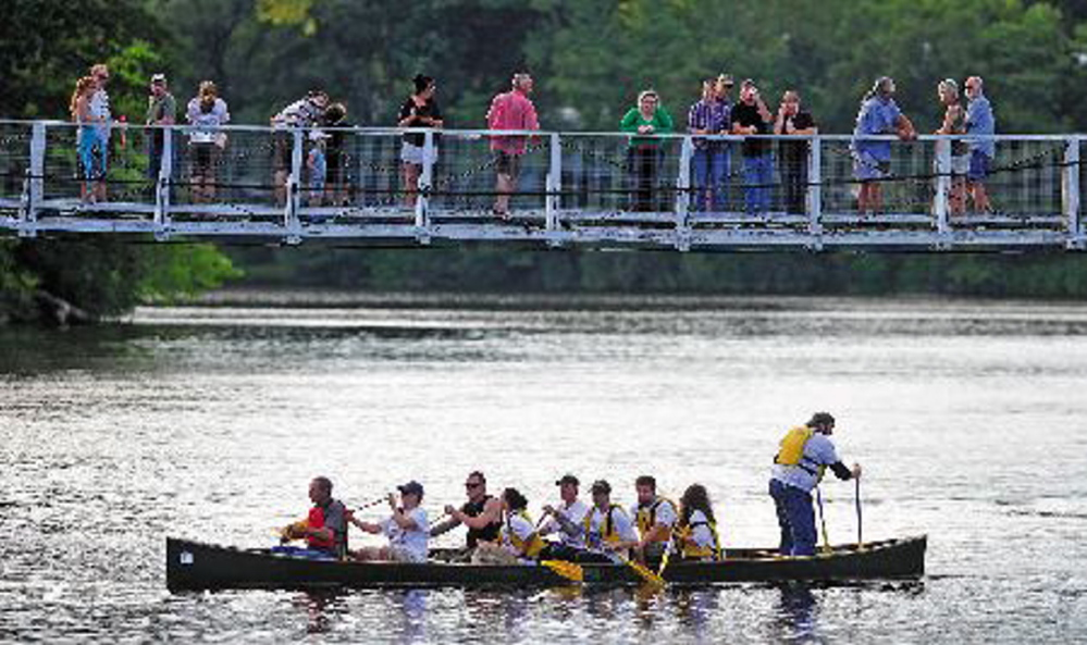The winning New Balance team crosses the finish line at the suspension bridge in the 2013 Skowhegan River Fest boat races on the Kennebec River. The races will once again be part of Skowhegan's annual River Fest.