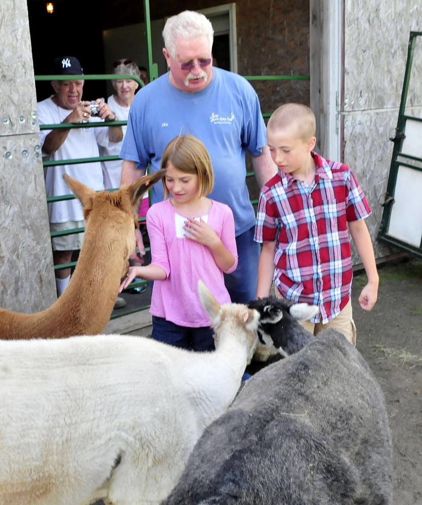 Misty Acres Alpaca Farm owner Red Laliberte watches as Madeline and Corbin Kissinger feed alpacas during the statewide Open Farm Day at the Sidney farm on Sunday, July 27, 2014.