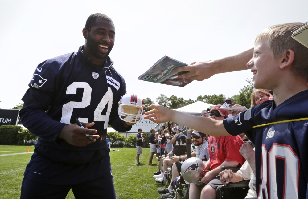 New England Patriots cornerback Darrelle Revis jokes with fans as he signs autographs after training camp Friday in Foxborough, Mass.