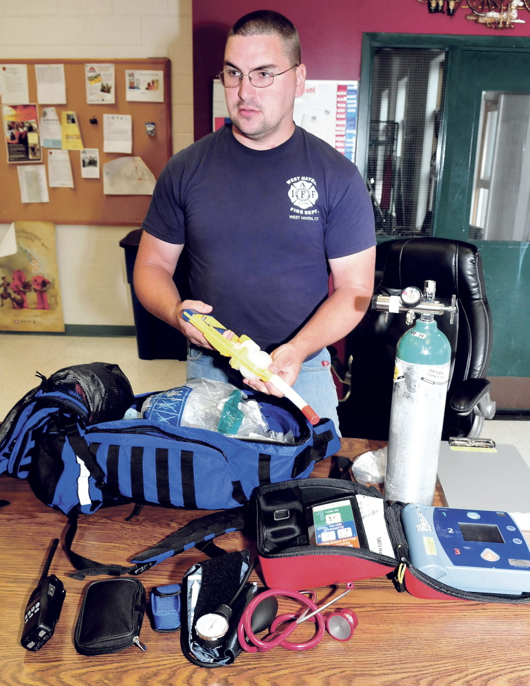 Dan Mayotte, a Waterville firefighter and an organizer of the Vassalboro First Responders group, shows the medical equipment he carries in his pack to people who need help.