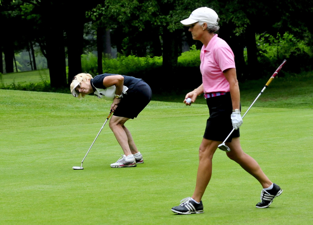 Debby Gardner, left, leans over hoping to coerce the ball she just hit roll closer to the hole during the Maine Women's Amateur at the Waterville Country Club in Oakland on Monday.