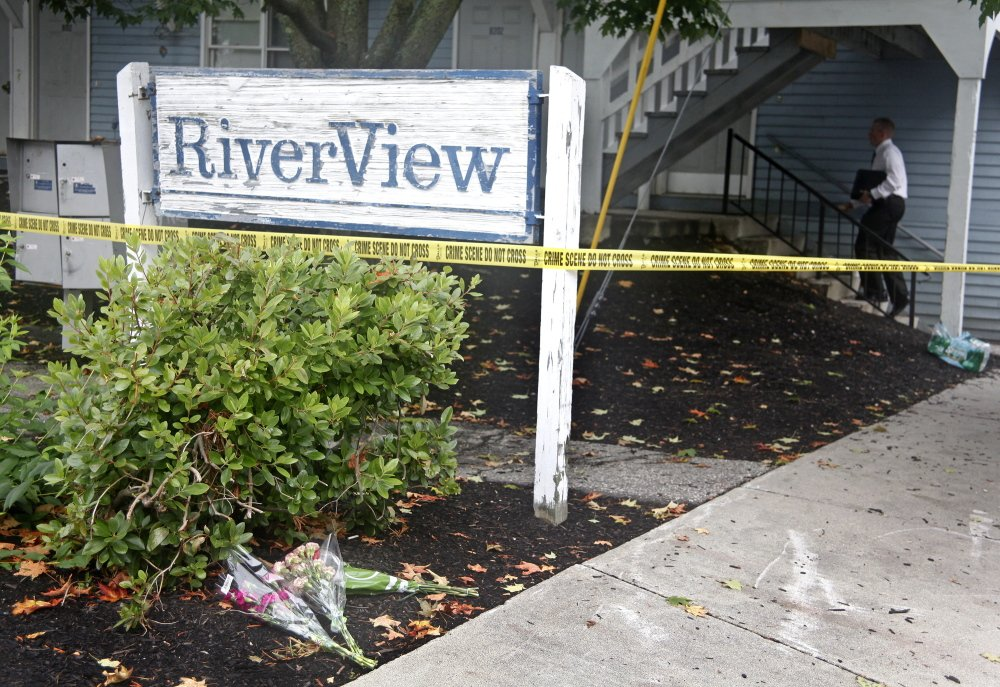 Press Herald photo by Jill Brady Bouquets of flowers rest at the RiverView apartment building sign as an investigator climbs the stairs to the apartment where five members of one family were found dead at 27 Water St., Saco, on Sunday.