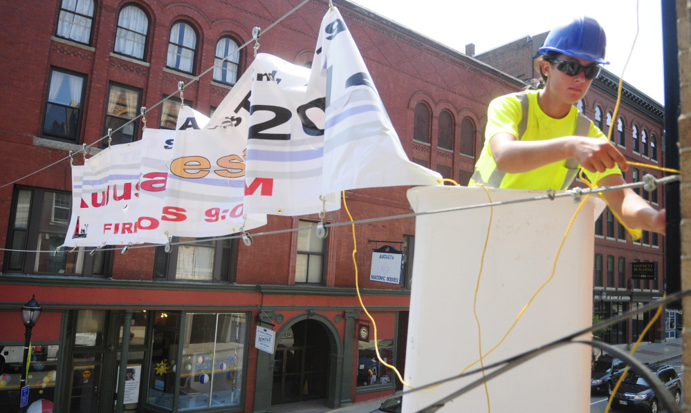 Megan Lovley works on a boom truck outside a window of The Gin Mill in downtown Augusta to hang a banner for AugustaFest, which takes place on Saturday.