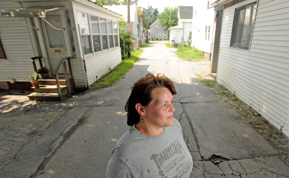 Betty Hovey, 40, stands on Carey Lane on Friday. A man was stabbed at a house on the street earlier in the week.
