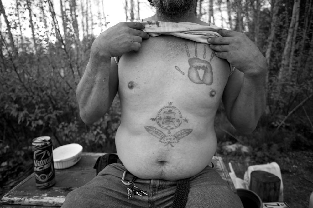Ira Gilbert, a member of the Passamaquoddy tribe, shows the tattoos he got while in prison in Arizona. Today, Gilbert and his three dogs live in a mobile home on tribal land. Blame spread to many people in leadership roles in the 1980s and '90s when votes for a tribal constitution ended in defeat.