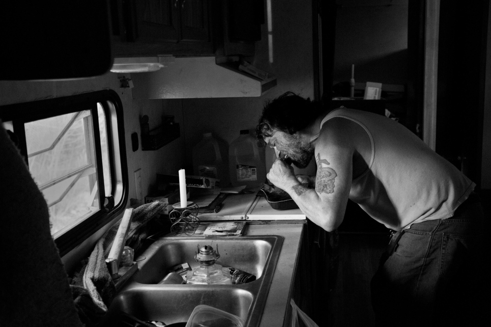 Ira Gilbert, an unemployed Passamaquoddy tribal member, bites into a frozen Salisbury steak dinner that he shared recently with his three dogs at his rustic home in Indian Township. Poverty persists on the reservation; a Harvard University study suggests that economic success among American Indians is linked to a stable rule of law.