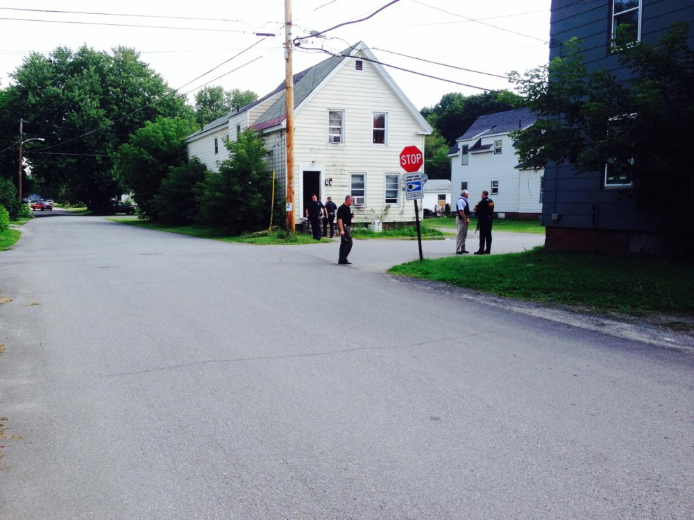 Police officers stand outside 25 Spruce St. in Waterville, where a man who threated to point a gun at point surrendered after a standoff lasting about 40 minutes.