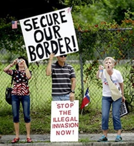 Demonstrators hold signs and yell outside the Mexican Consulate Friday, July 18, 2014, in Houston.   Prospects for action on the U.S.-Mexico border crisis faded Thursday as lawmakers traded accusations rather than solutions, raising chances that Congress will go into its summer recess without doing anything about the tens of thousands of migrant children streaming into South Texas.  (AP Photo/David J. Phillip)