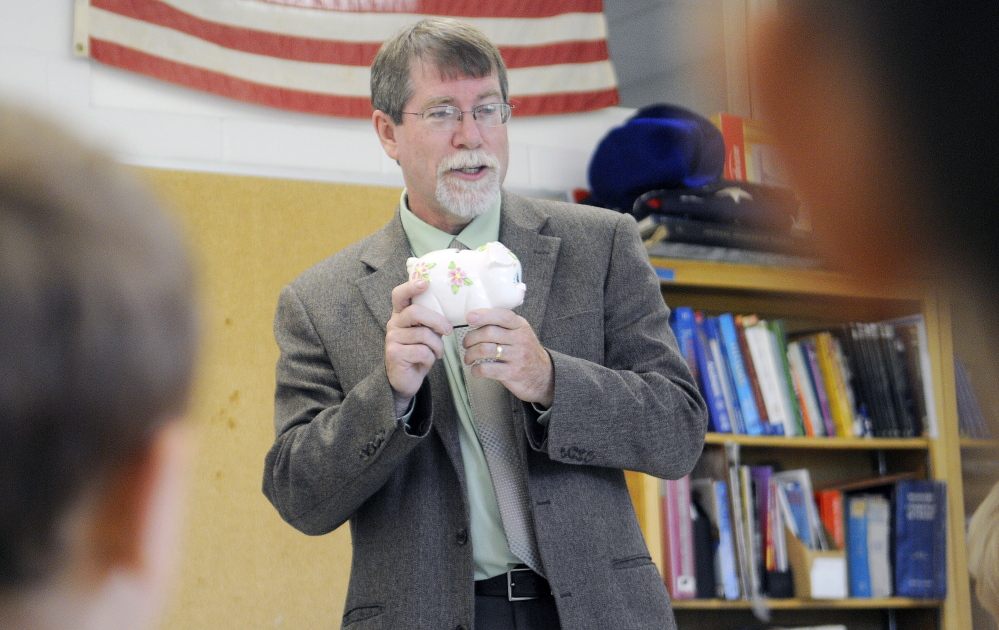 Assistant Attorney General Steve Parker clutches a piggy bank last week while speaking to Augusta elementary school students at Cony High School about the importance of understanding mathematics.