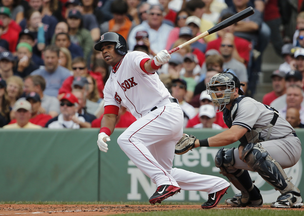 Boston's Yoenis Cespedes follows through on a single in his first at-bat as a Red Sox player, as New York Yankees catcher Francisco Cervelli watches during the second inning Saturday at Fenway Park in Boston. Cespedes went 1 for 4 with a single.