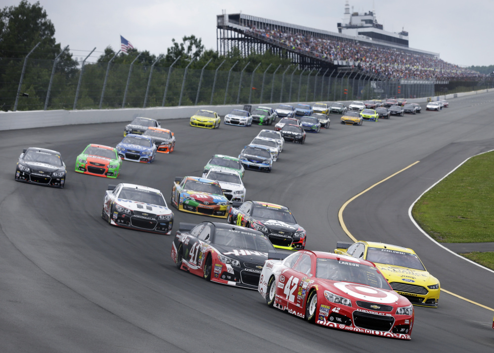 Kyle Larson (42) leads a pack of cars at the start of the NASCAR Sprint Cup Series auto race at Pocono Raceway, Sunday, Long Pond, Pa.