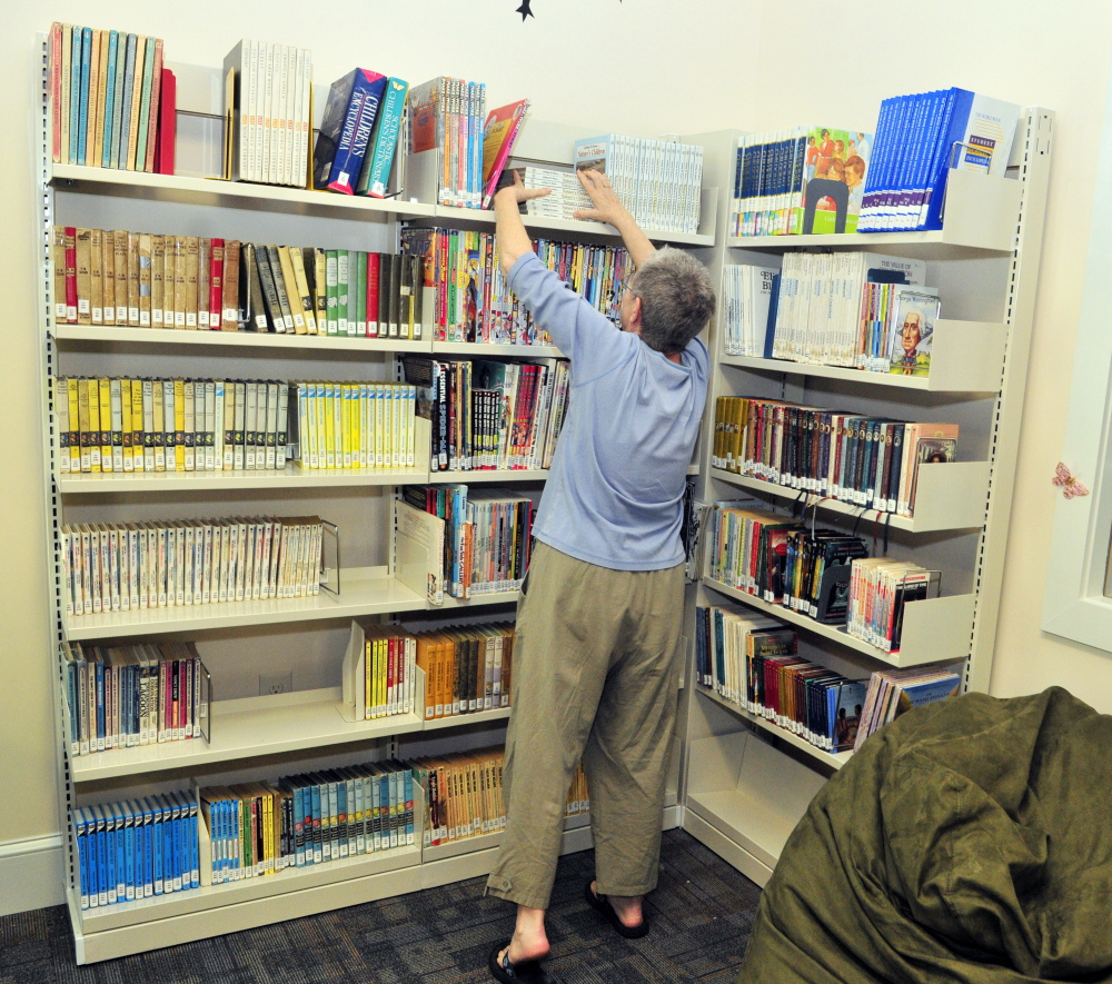 Board of trustees member Bonnie Dushin straightens books in the young adult area during a tour of new Umberhine Public Library on Thursday in Richmond.
