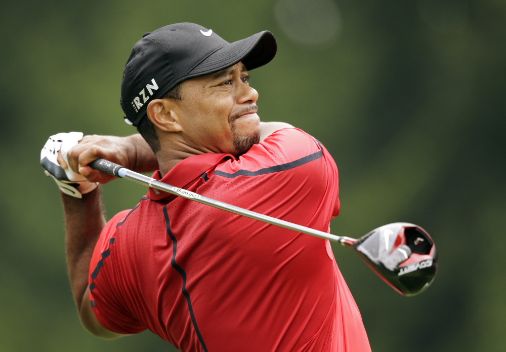 Tiger Woods watches his his tee shot on the fourth hole during the final round of the Bridgestone Invitational on Sunday at Firestone Country Club in Akron, Ohio. Woods withdrew from the tournament after experiencing back pain. Woods had returned to golf recently after recovering from back surgery.