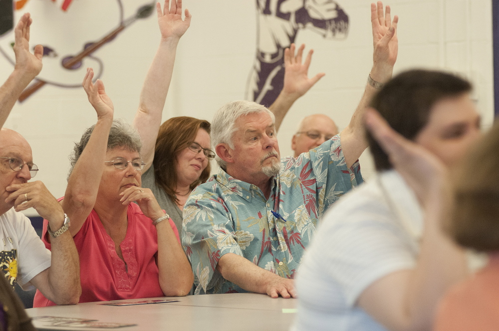 Members of Ward 6 vote with a show of hands during the Waterville Democratic caucus at Waterville Senior High School on Sunday.