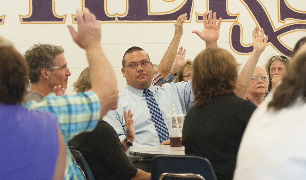 Members of Ward 2 vote with a show of hands during the Waterville Democratic caucus at Waterville Senior High School on Sunday.