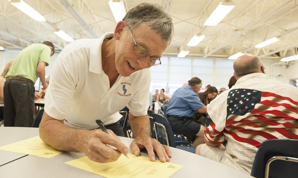 Steve Aucoin fills out paperwork after being nominated to run for mayor during the Waterville Democratic caucus at Waterville Senior High School on Sunday.
