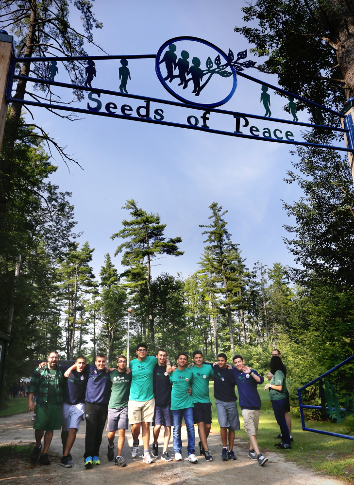 A group of campers join arms and sing songs as they make their way to opening ceremonies at Seeds of Peace.