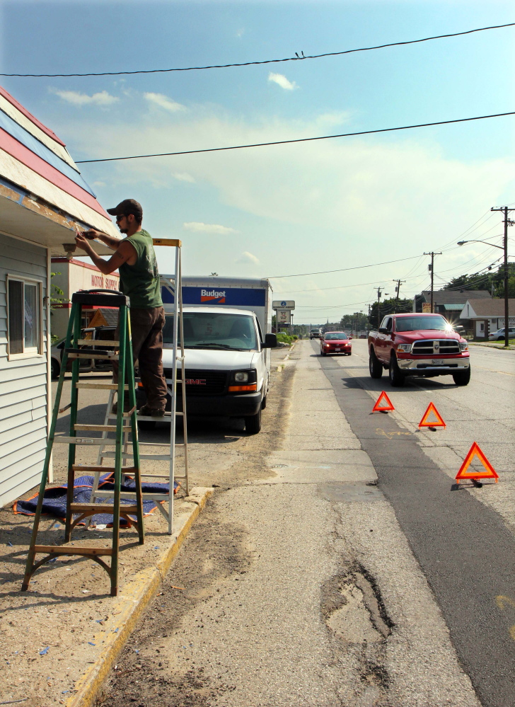 Martin Fernald prepares a former barber shop to be repainted as motorists drive up College Avenue in Waterville on Monday. College Avenue is one of several streets scheduled to be repaved.