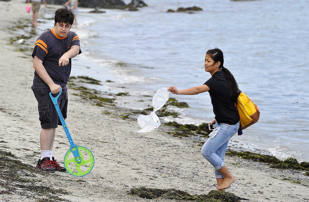 Zach Michaud, left, a second-year SMCC computer science student, is helped by Deering High School graduate Jazmine Abasta as they find the exact landing point of a one-gallon, water-filled projectile.