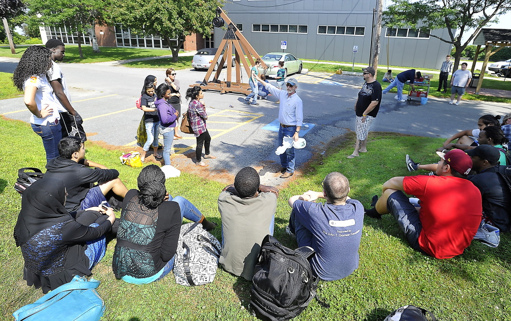 SOUTH PORTLAND, ME - AUGUST 4: With the catapult device called a trebuchet in the background, Associated Professor Kevin D. Kimball explains the details of the physics exercise to the students as Portland and Deering high school students participate in a summer prep course at SMCC and complete it by participating in a physics project involving a trebuchet. (Gordon Chibroski/Staff Photographer)