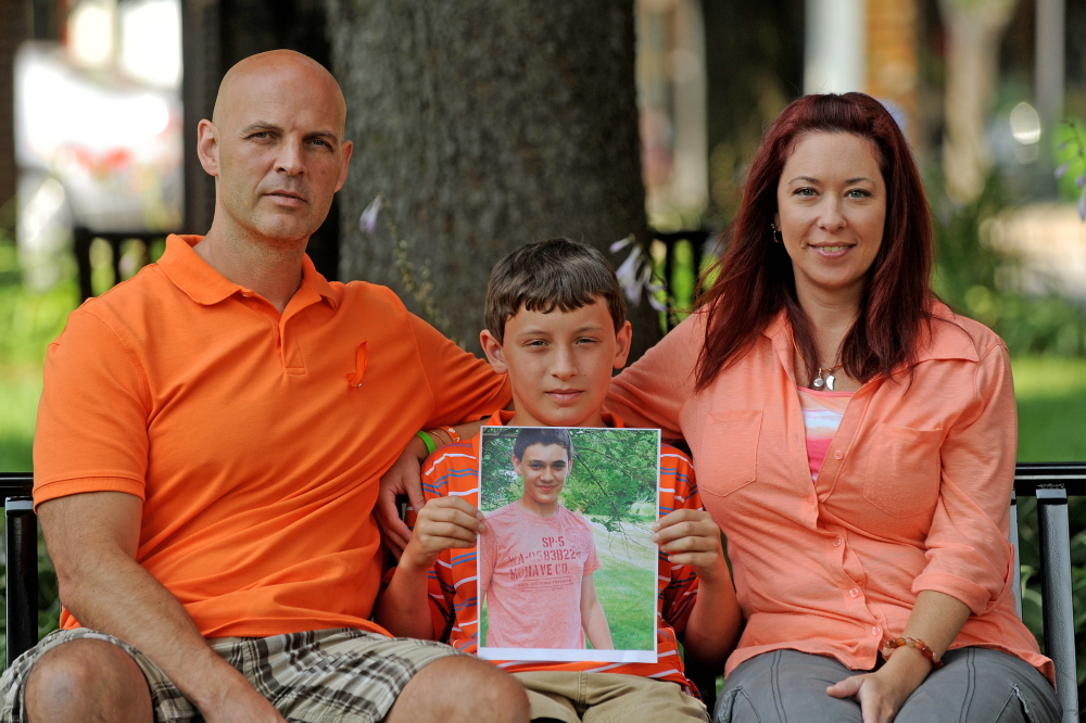 Ray, Nason and Amy Berthelette sit with a picture of Nolan at Castonguay Square in downtown Waterville on Tuesday.