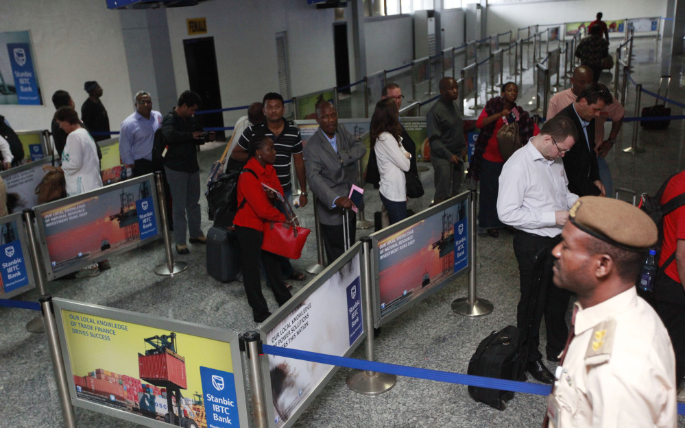Passengers queue for their passport document check by immigration officers at the arrivals hall of Murtala Muhammed International Airport in Lagos, Nigeria, Monday.