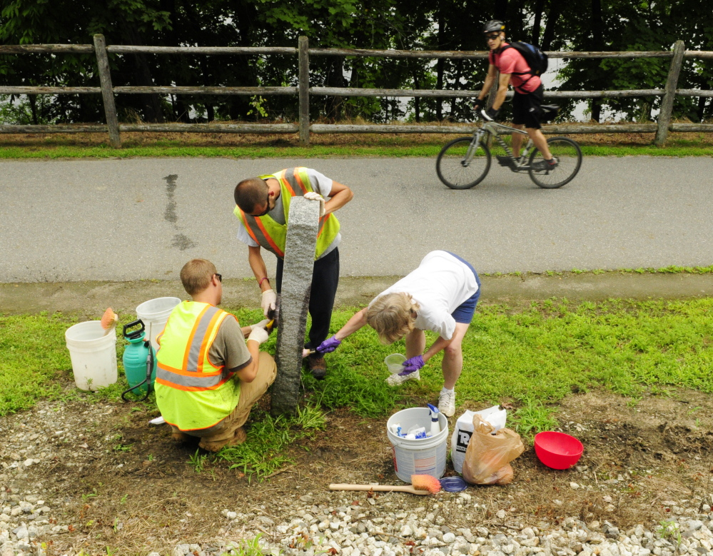 "A passing cyclist watches city workers Taylor Perry, left, and Shawn Winslow and volunteer Kathleen ""Sukey"" Sikora remove graffiti from a Kennebec River Rail Trail milestone on Wednesday in Augusta."