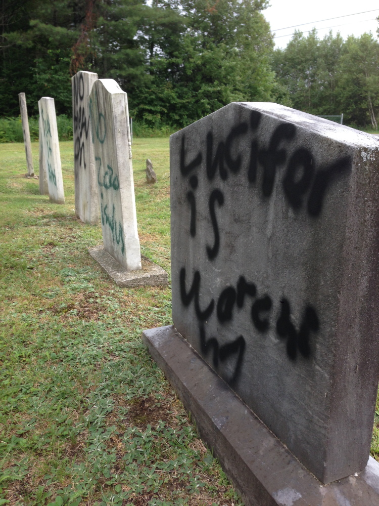 """Lucifer is watching,"" proclaims a message spray-painted on a gravestone in Pleasant View Ridge Cemetery in China on Wednesday."