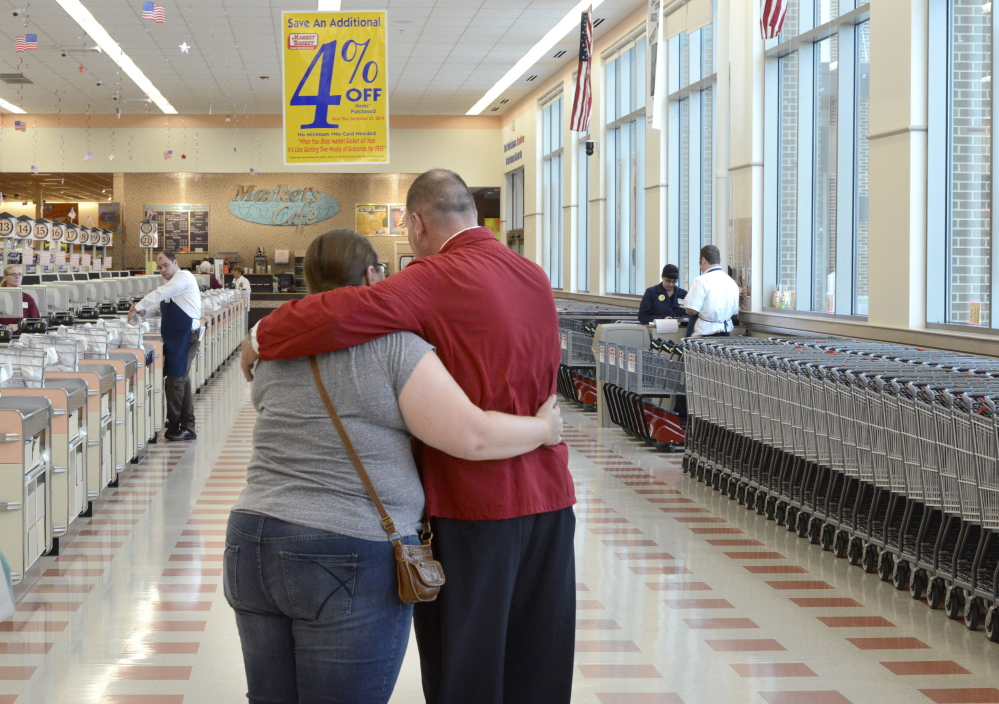 "A supervisor, in red coat, comforts a part-time worker who learned Thursday that her hours were being reduced or eliminated at the Market Basket in Biddeford. ""Customers just stopped coming in. If there's no one in the store, we're not able to use part-timers,"" said Micum McIntire, the store manager."