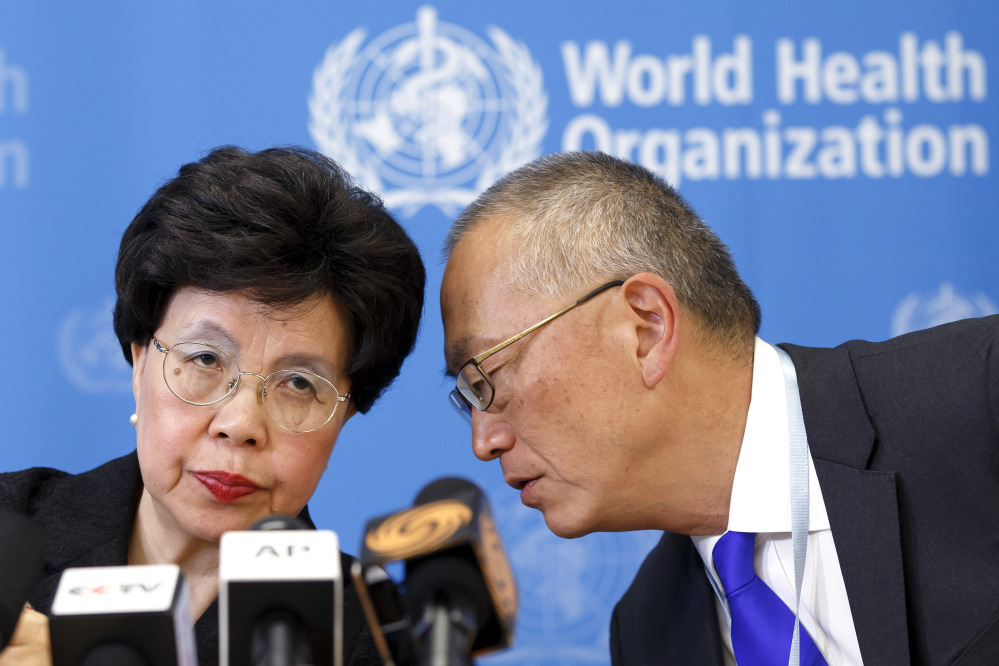 The director general of the World Health Organization, China's Margaret Chan, and Assistant Director General for Health Security Keiji Fukuda of the U.S., right, share a word during a news conference after an emergency meeting at the headquarters of the WHO in Geneva, Switzerland, on Friday.