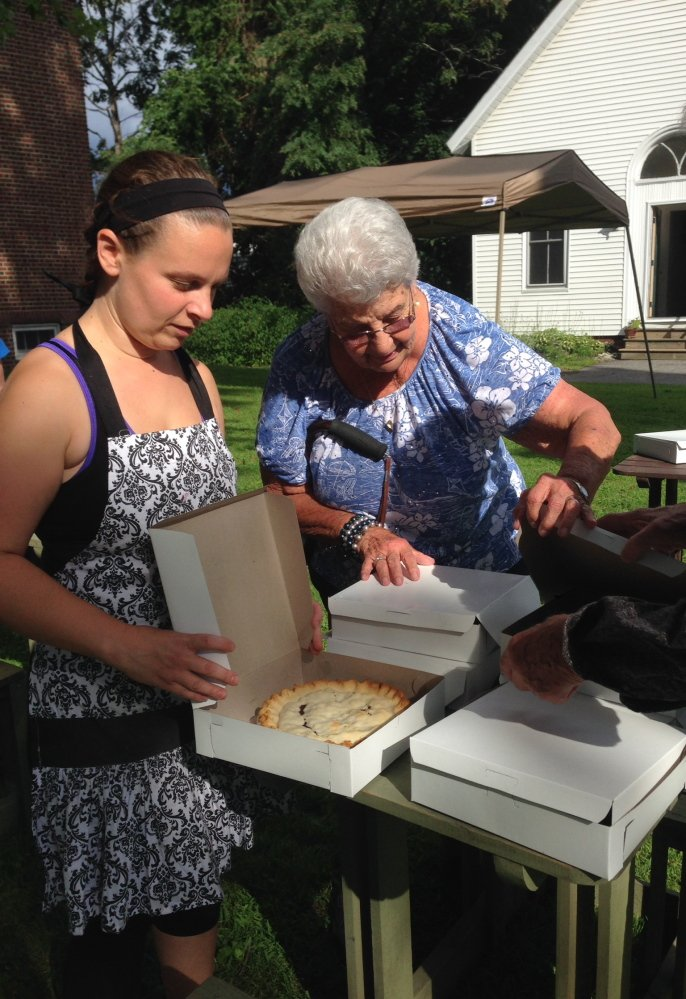 Normal (Web):Pauline Poulin, right inspects a table of blueberry pies staffed by Amy Fogg Friday night at Winslow Congregational Church. The church is hosting its 43rd annual Blueberry Festival on Saturday.