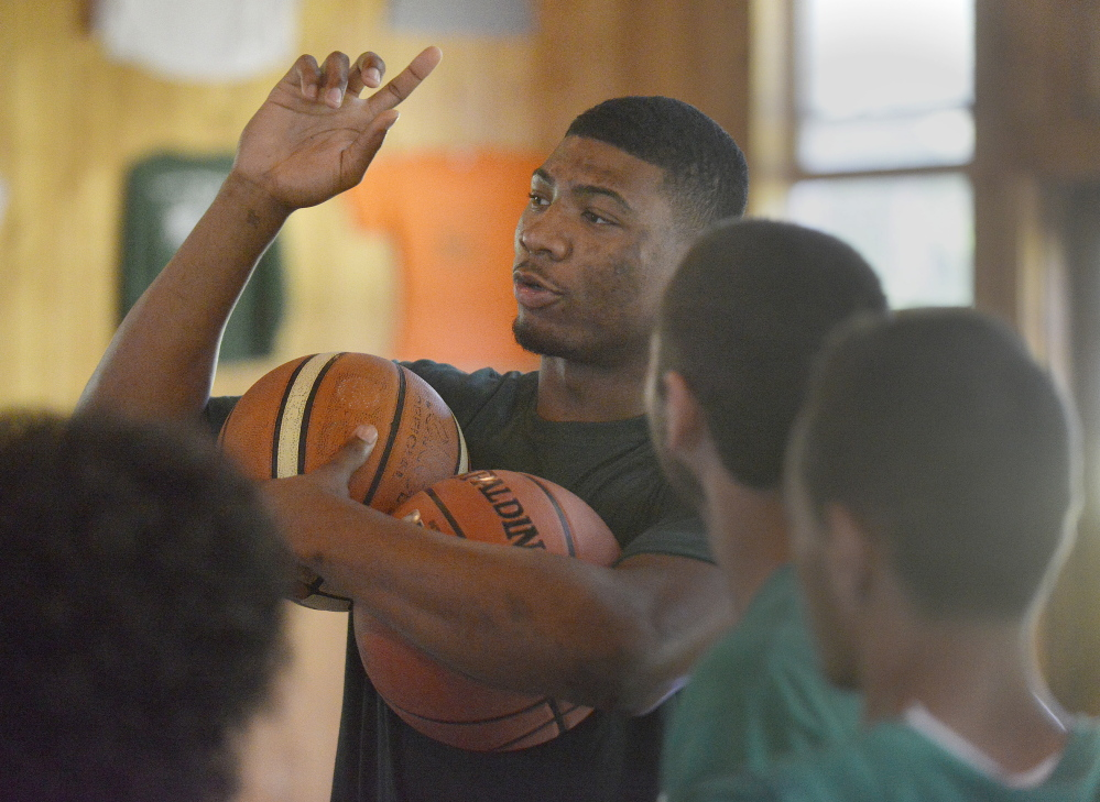 Portland Press Herald photo by John Ewing NBA basketball players including Boston Celtic first round pick Marcus Smart, participated in the Seeds of Peace's annual Play of Peace program at the Otisfield summer camp. Smart instucts some of the participating campers in how to do a ball handling drill.