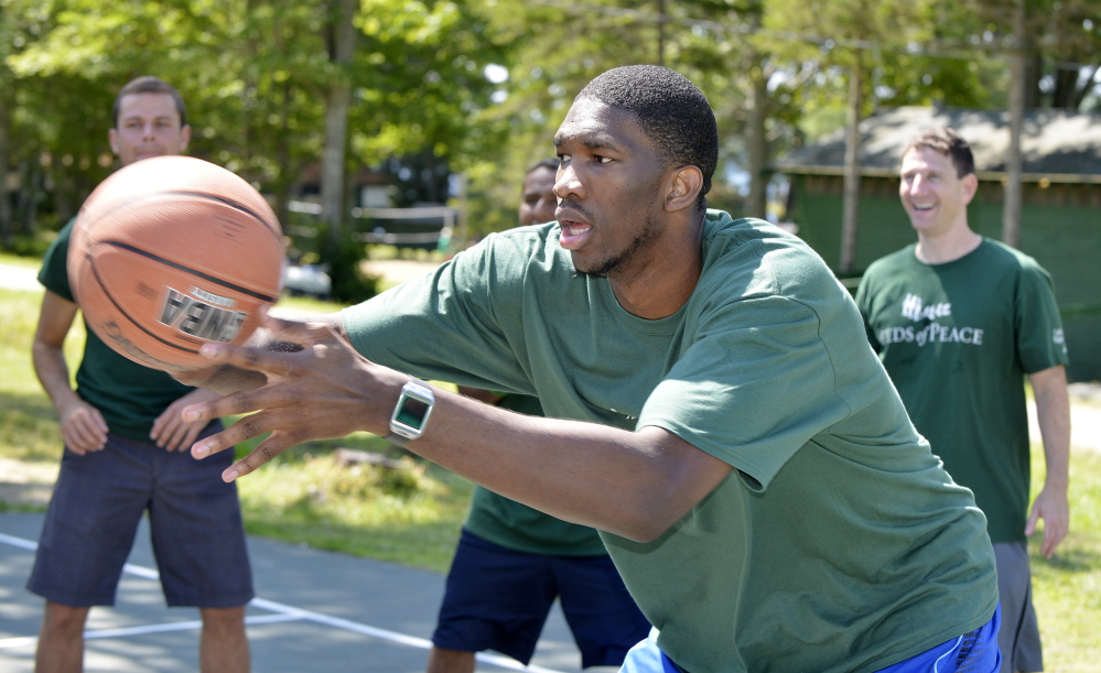 Portland Press Herald photo by John Ewing NBA basketball players including Boston Celtic first round pick Marcus Smart, participated in the Seeds of Peace's annual Play of Peace program at the Otisfield summer camp. NBA rookie Joel Embiid participates in some passing drills with the campers.)