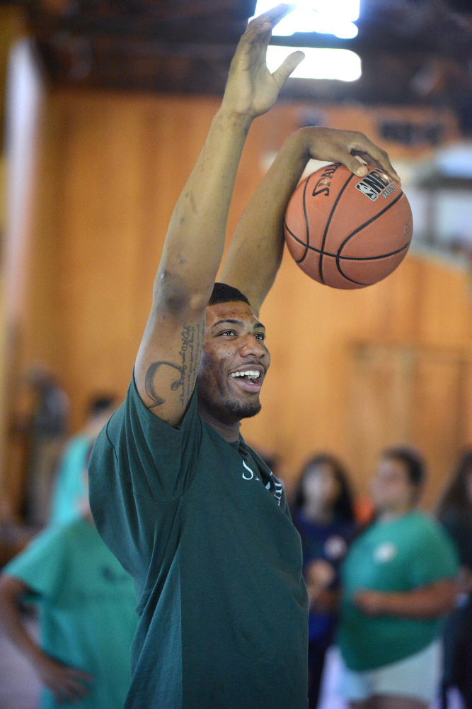 Portland Press Herald photo by John Ewing Marcus Smart celebrates a camper's basket while running a layup drill at the clinic.
