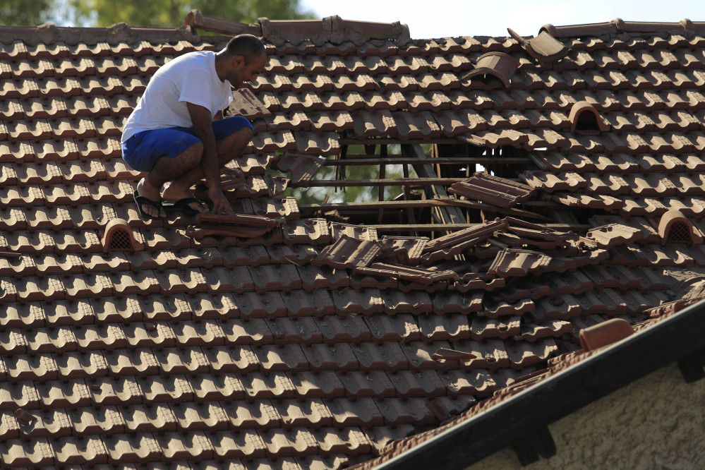 An Israeli man examines the damage to the roof of his house after a rocket fired from Gaza hit in a residential neighborhood of the southern city of Sderot, Israel, Friday.