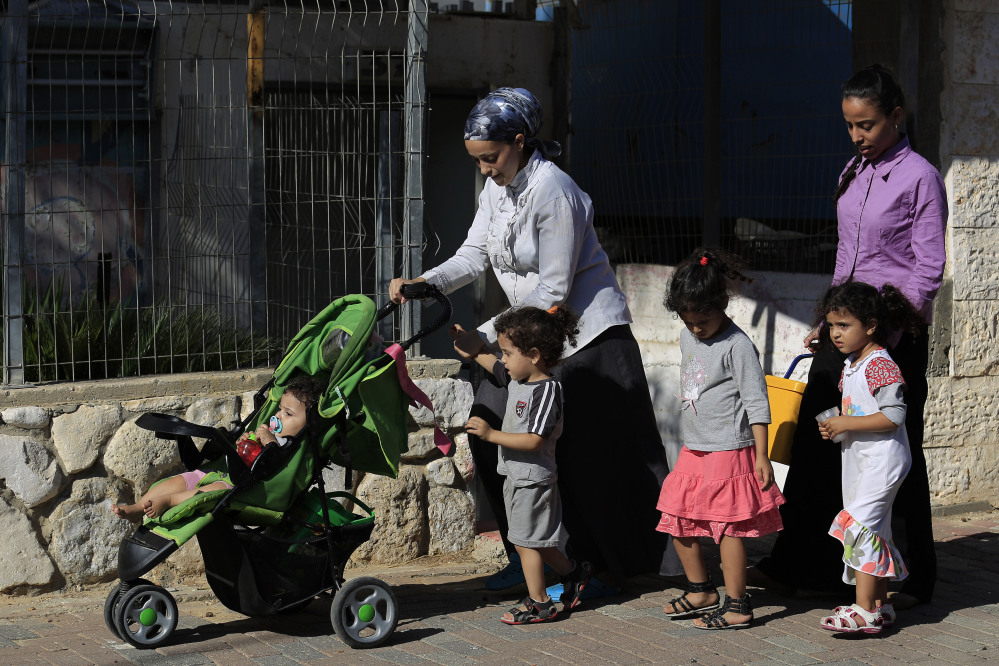 Israeli people flee from an area after a rocket fired from Gaza hit in a residential neighborhood of the southern city of Sderot, Israel, Friday.