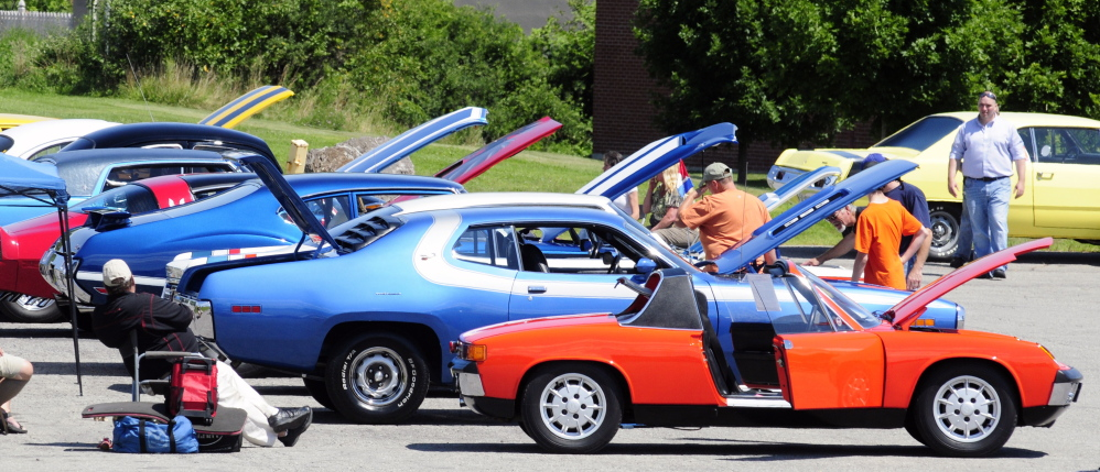 Spectators look at row of cars from the 1970s during a car show Saturday in the Augusta Civic Center parking lot. The event was a fundraiser for the Maine Children's Cancer Program.