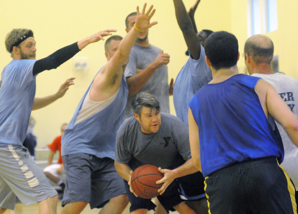 Nate Munzing is swarmed by defenders during a YMCA summer league basketball game Wednesday.