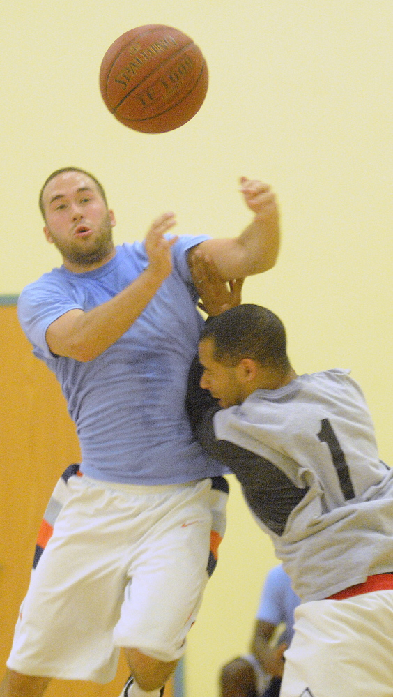 Josh Berard, right, blocks Jay Dangler during a summer league basketball game Wednesday at the YMCA in Augusta.
