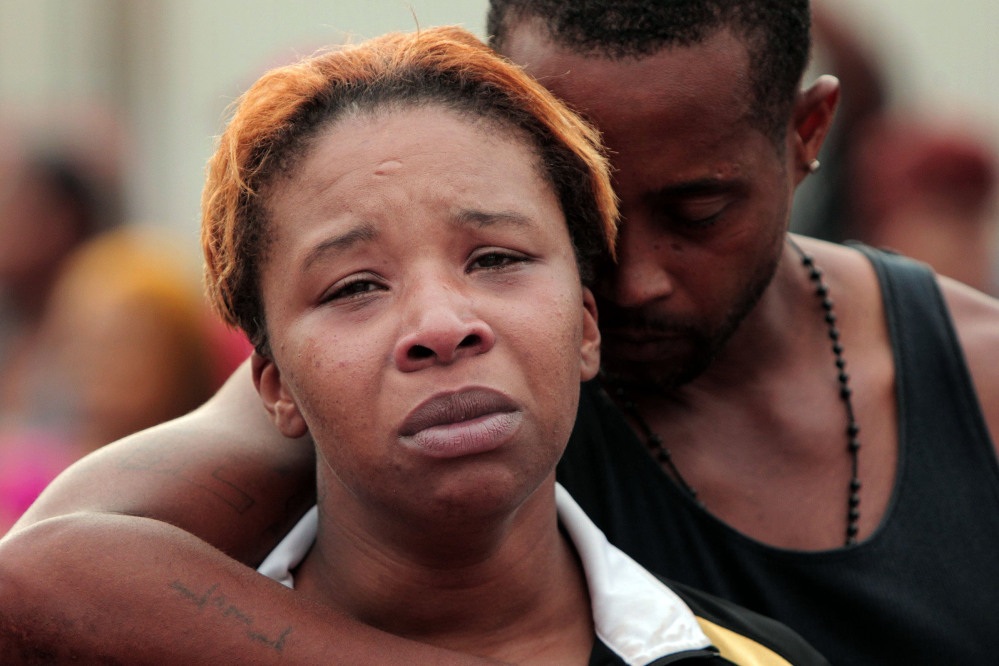 Lesley McSpadden, left, is comforted by her husband, Louis Head, after her 18-year-old son, Michael Brown was shot by police and killed in the middle of the street in Ferguson, Mo., near St. Louis on Saturday.
