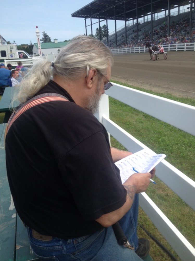 Lawrence Murray, of Fairfield, marks his bet during harness racing Sunday during the 196th annual Skowhegan State Fair.